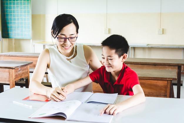 Unterrichtender junge des lehrers, zum von hausaufgaben im klassenzimmer zu tun Premium Fotos