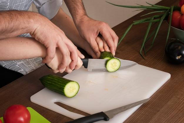 Unterrichtender sohn des nahaufnahmevaters, zum des gemüses zu schneiden Kostenlose Fotos