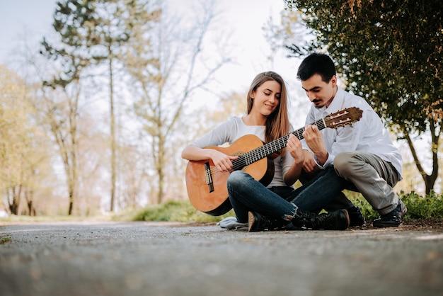 Unterrichtendes mädchen des kerls, wie man gitarre am park spielt. Premium Fotos