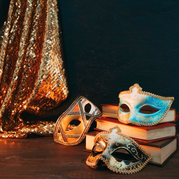 Unterschiedliche art der maske des karnevals drei auf stapel büchern mit funkelnpaillettegewebe über hölzernem schreibtisch Kostenlose Fotos