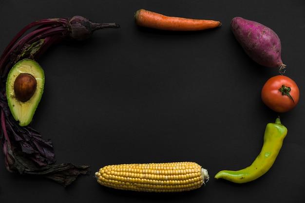 Unterschiedliche art des gesunden rohen lebensmittels, das rahmen auf schwarzem hintergrund bildet Kostenlose Fotos