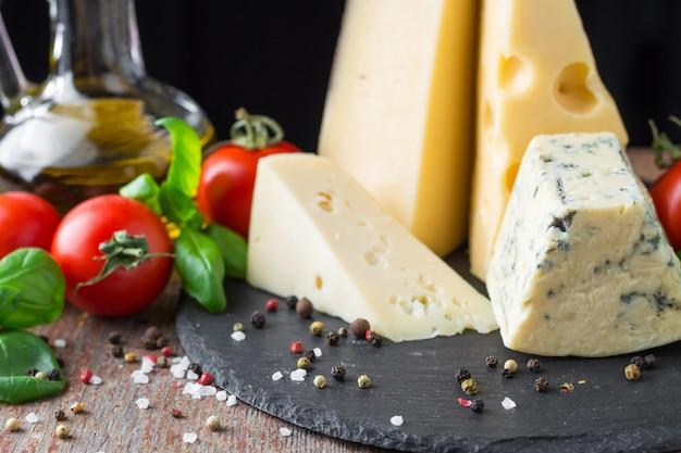Unterschiedliche art des käses, der tomate und des basilikums auf einem holztisch. vegetarisches essen Premium Fotos