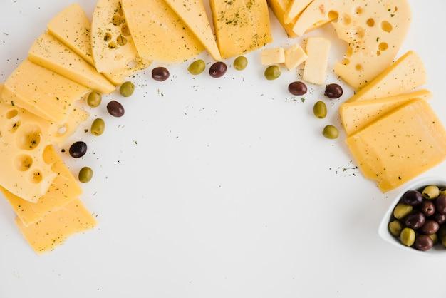 Unterschiedliche art von käsescheiben mit oliven auf weißem hintergrund Kostenlose Fotos