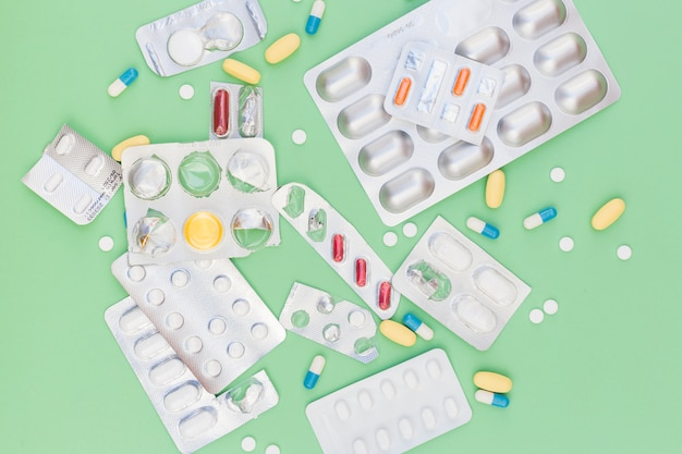 Unterschiedliche art von medizinischen pillen aus blase heraus verpackt gegen grünen hintergrund Kostenlose Fotos