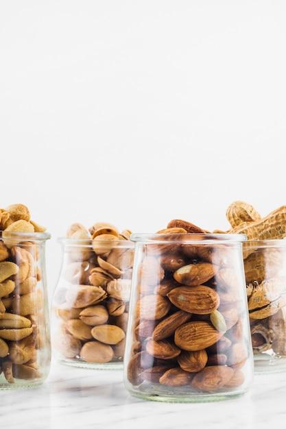 Unterschiedliche art von nussnahrungsgläsern auf marmoroberfläche Kostenlose Fotos