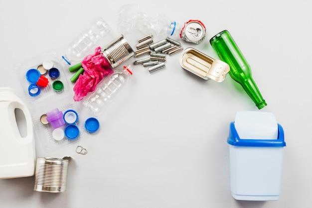 Unterschiedlicher recycelbarer abfall, der in mülltonne gießt Kostenlose Fotos