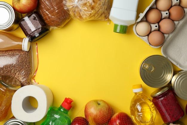 Unterschiedliches essen auf gelbem raum, draufsicht. spendenkonzept Premium Fotos