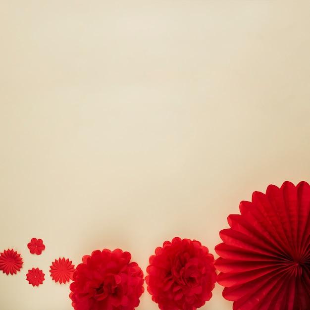 Unterschiedliches muster des roten origamiblumenausschnitts auf beige hintergrund Kostenlose Fotos