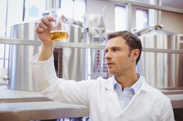 Untersuchungsbecher des fokussierten wissenschaftlers mit bier Premium Fotos