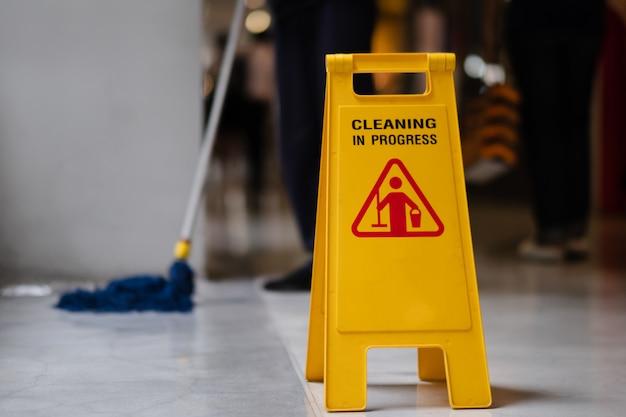 Unterzeichnen sie das zeigen der warnung des nassen bodens der vorsicht im flughafen. Premium Fotos