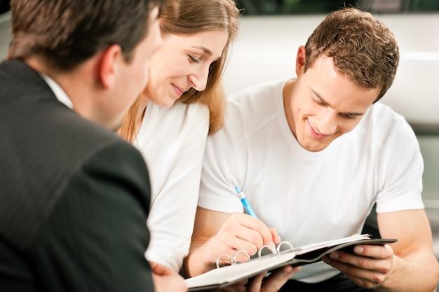 Unterzeichnender kaufvertrag der paare am autohändler Premium Fotos