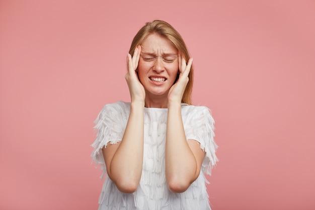 Unzufriedene junge rothaarige dame mit lässiger frisur runzelte mit geschlossenen augen die stirn und hielt die finger an ihren schläfen, isoliert über rosa hintergrund Kostenlose Fotos