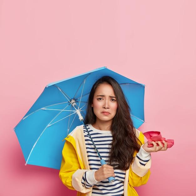 Unzufriedene koreanerin hält taschentuch, erkältet bei kaltem regenwetter, hat laufende nase, versteckt sich unter regenschirm Kostenlose Fotos