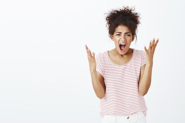 Unzufriedene wütende frau mit afro-frisur posiert im studio Kostenlose Fotos
