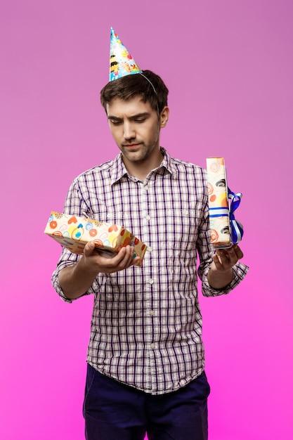 Unzufriedener junger hübscher mann, der geburtstagsgeschenk über lila wand öffnet. Kostenlose Fotos