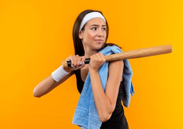 Unzufriedenes junges hübsches sportliches mädchen, das stirnband und armband mit handtuch auf ihrer schulter trägt, baseballschläger hält und seite lokalisiert auf orange raum betrachtet Kostenlose Fotos