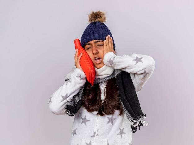 Unzufriedenes junges krankes mädchen mit geschlossenen augen, die wintermütze mit schal tragen heißes sackwasser auf wange setzen Kostenlose Fotos
