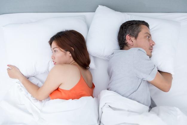 Upset young couple liegen im bett back to back Kostenlose Fotos