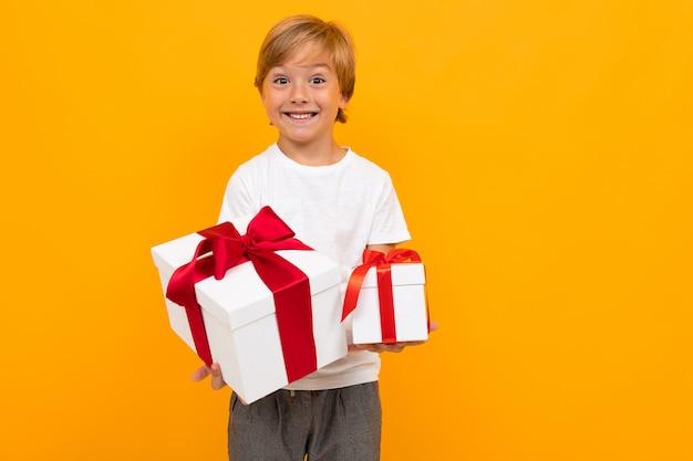 Urlaub . attraktiver junge hält eine box mit einem geschenk mit einem roten band auf einem hellen gelb Premium Fotos