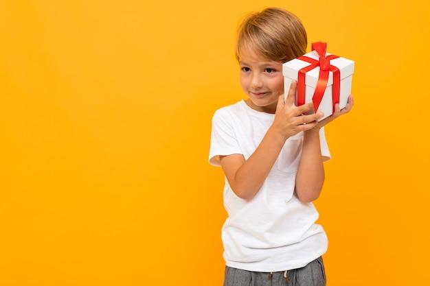 Urlaub . attraktiver junge mit geschenkbox auf hellem gelb Premium Fotos