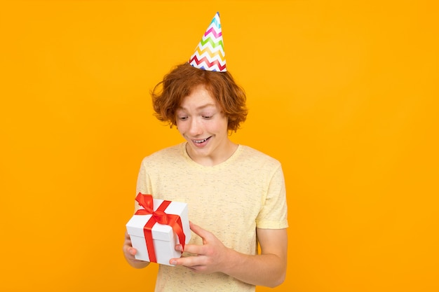 Urlaub . glücklich überrascht rothaarige junge mit einem geschenk in seinen händen auf einer orange Premium Fotos