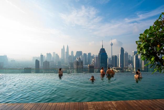 Urlaub in kuala-lumpur. junge frau genießen, im dachspitzenpool mit schöner stadtansicht zu schwimmen Premium Fotos