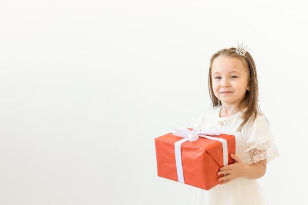 Urlaub und präsentiert konzept. kleines mädchen lächelt und hält rote geschenkbox auf weiß Premium Fotos