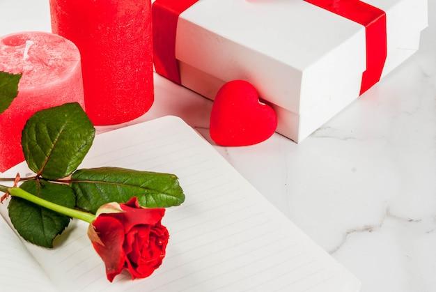 Urlaub, valentinstag. strauß roter rosen, krawatte mit roter schleife, mit leerem notizblock, umwickelter geschenkbox und roter kerze. auf einer weißen marmortabelle copyspace draufsicht Premium Fotos