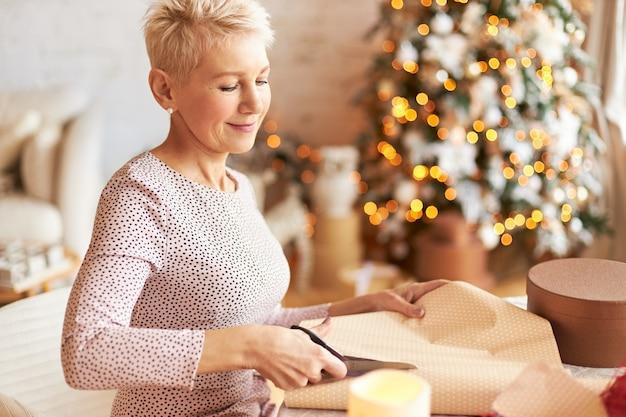 Urlaubs-, feier- und urlaubskonzept. elegante schöne reife frau mit kurzen haaren, die im dekorierten wohnzimmer mit weihnachtsbaum aufwirft und geschenkverpackung mit schere schneidet Kostenlose Fotos