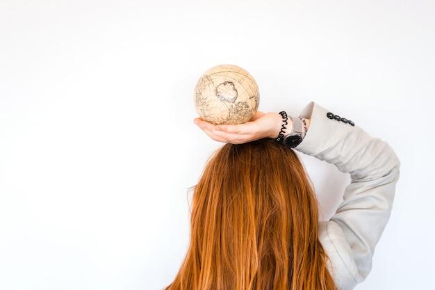 Urlaubsreisen-sommerwochenenden-abenteuerreisekonzept. rotes haarmädchen, das antike kugel der weinlese lokalisiert auf weißem hintergrund hält. kopieren sie platz. mock up für turism agency. bildungs- und entdeckungsidee Premium Fotos