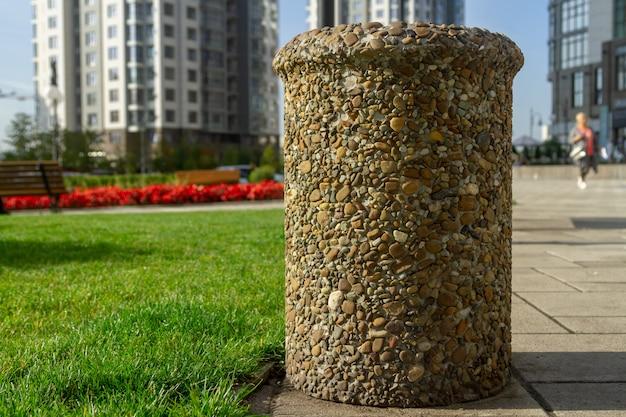 Urne für müll, mit glatten steinen beklebt. ungewöhnliche stadtstraße mülleimer. Premium Fotos