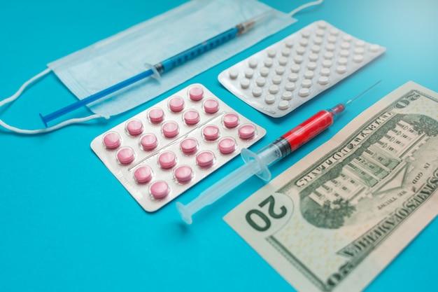 Us-dollar-banknoten. medizinische maske, impfstoffspritze und rosa pillen, pillenblase. wirtschaftskrise. gesundheitsausgaben. ausbruch des coronavirus. Premium Fotos