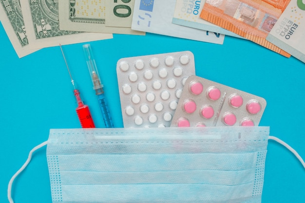 Us-dollar und euro-banknoten. medizinische maske, impfstoffspritze und rosa pillen, pillenblase. wirtschaftskrise. gesundheitsausgaben. ausbruch des coronavirus. Premium Fotos