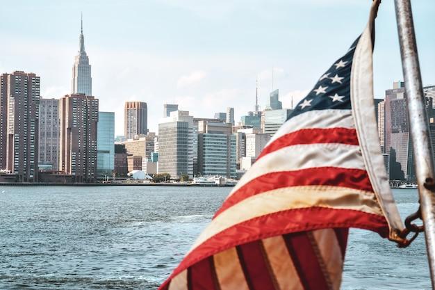 Us-flagge im vordergrund und bürogebäude und wohnungen auf der skyline bei sonnenuntergang. immobilien- und reisekonzept. manhattan, new york city, usa. Premium Fotos