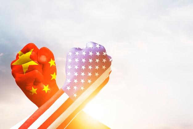 Usa- und china-flaggendruckschirm auf armdrücken mit himmel. vereinigte staaten von amerika gegen china-handelskrieg bestreitet konzept. Premium Fotos