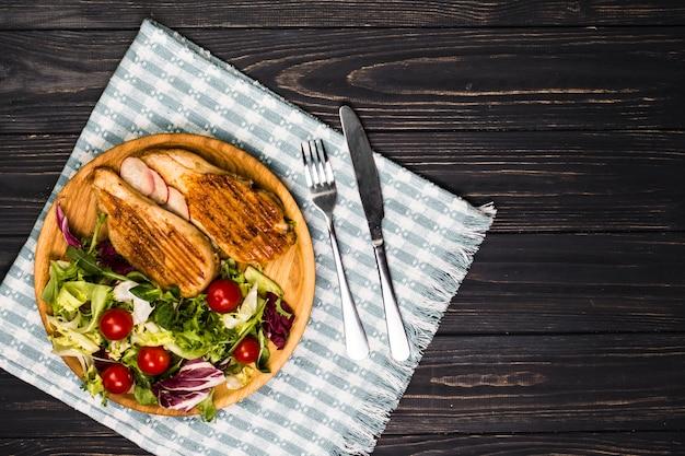 Utensilien in der nähe von gebratenem hähnchen und salat Kostenlose Fotos