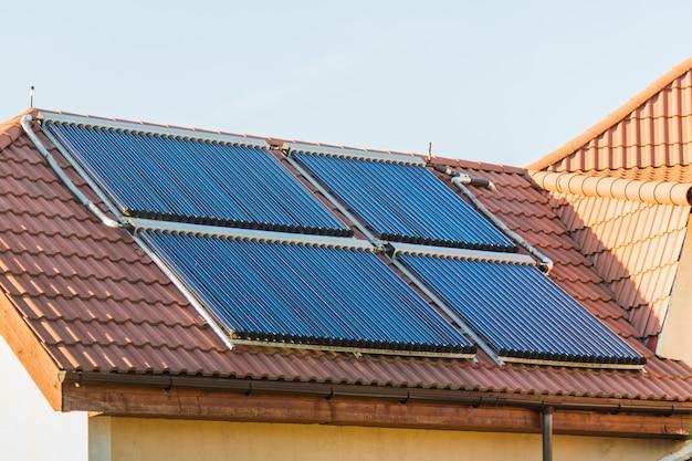Vakuumkollektoren - solarwarmwasserbereitungsanlage auf rotem dach des hauses Premium Fotos