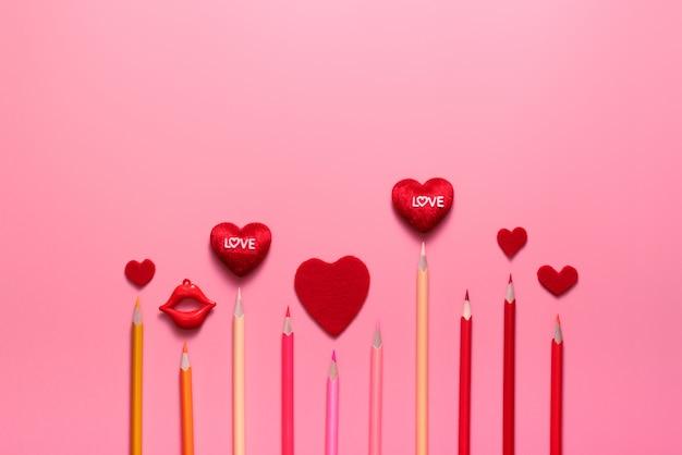 Valentine day-konzept, rote herzen und farbbleistift auf rosa hintergrund Premium Fotos