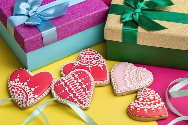 Valentine lebkuchen auf hellem hintergrund und geschenkboxen mit bändern. Premium Fotos