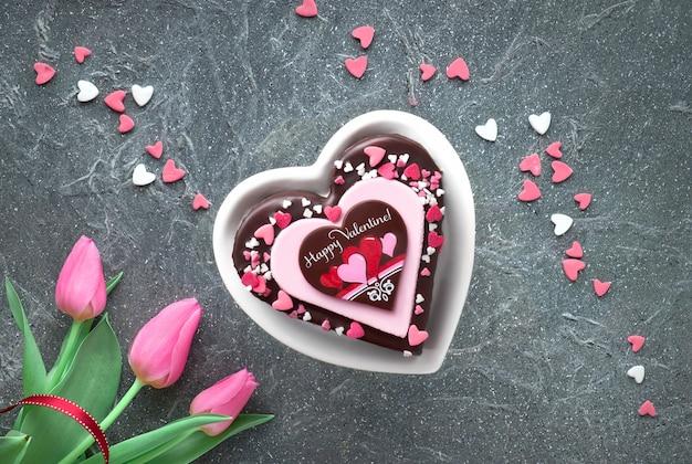 Valentinsgrußherzkuchen mit schokoladen- und zuckerdekorationen Premium Fotos