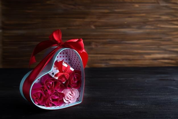 Valentinsgrußhintergrund mit roten herzen und stieg in geschenkbox auf dunklem hölzernem hintergrund Premium Fotos