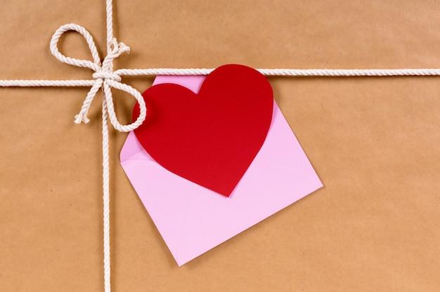 Valentinsgrußkarte auf einem braunen papierpaket oder einem geschenk gebunden mit schnur. Kostenlose Fotos