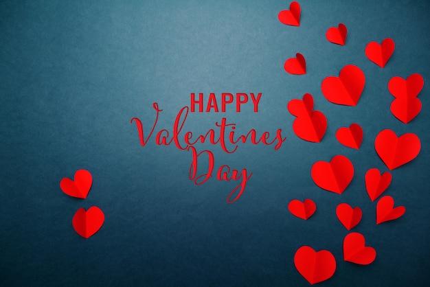 Valentinsgrußkarte mit rotem herzen auf blauem hintergrund, abstrakte, flache lage, draufsicht Premium Fotos