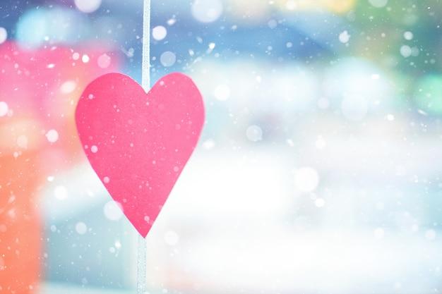 Valentinstag an einem schneebedeckten wintertag. dekor aus geschnitztem rotem papier in form eines herzens Premium Fotos