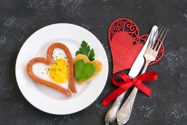 Valentinstag das frühstück besteht aus rührei mit herzförmigem brot. Premium Fotos