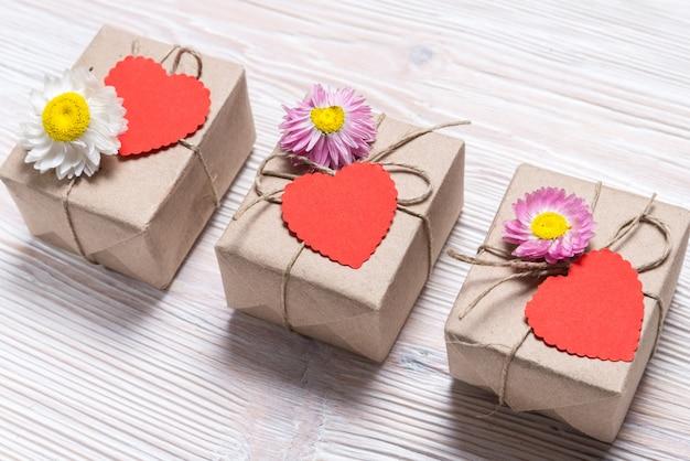 Valentinstag drei geschenkboxen auf hölzernem hintergrund Premium Fotos