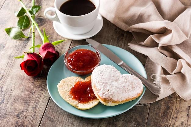 Valentinstag frühstück mit kaffee herzförmigen brötchen und beerenmarmelade Premium Fotos