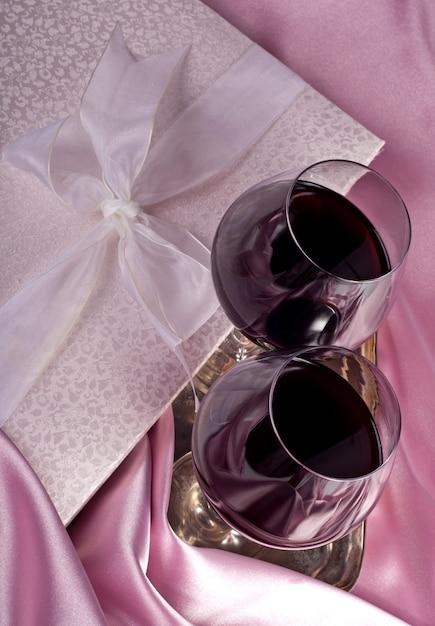 Valentinstag. geschenkbox, blumen, gläser mit wein auf dem rosa farbhintergrund Premium Fotos