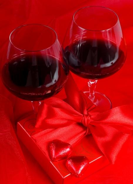 Valentinstag. geschenkbox, blumen, gläser mit wein und süßigkeiten in form eines herzens auf rotem grund Premium Fotos
