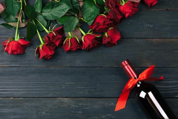 Valentinstag-grußkarte. rotrosenblumen, wein und geschenkbox auf holztisch. Premium Fotos